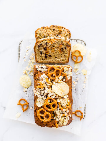 Christina Tosi's compost pound cake rectangular loaf cake with potato chips, pretzels, chocolate chips, butterscotch chips, oats, and coffee, on a small cooling rack on parchment paper