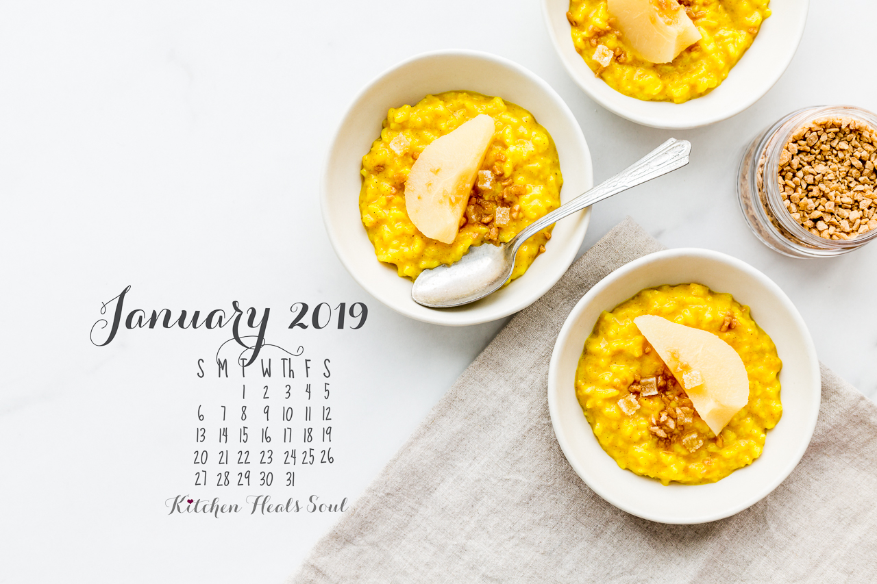 January 2019 desktop calendar featuring bowls of yellow golden milk rice pudding topped with poached pears, maple flakes, and crystallized ginger