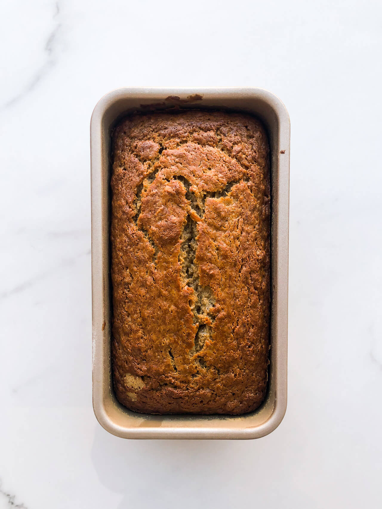 Baked golden brown banana bread in a loaf cake pan