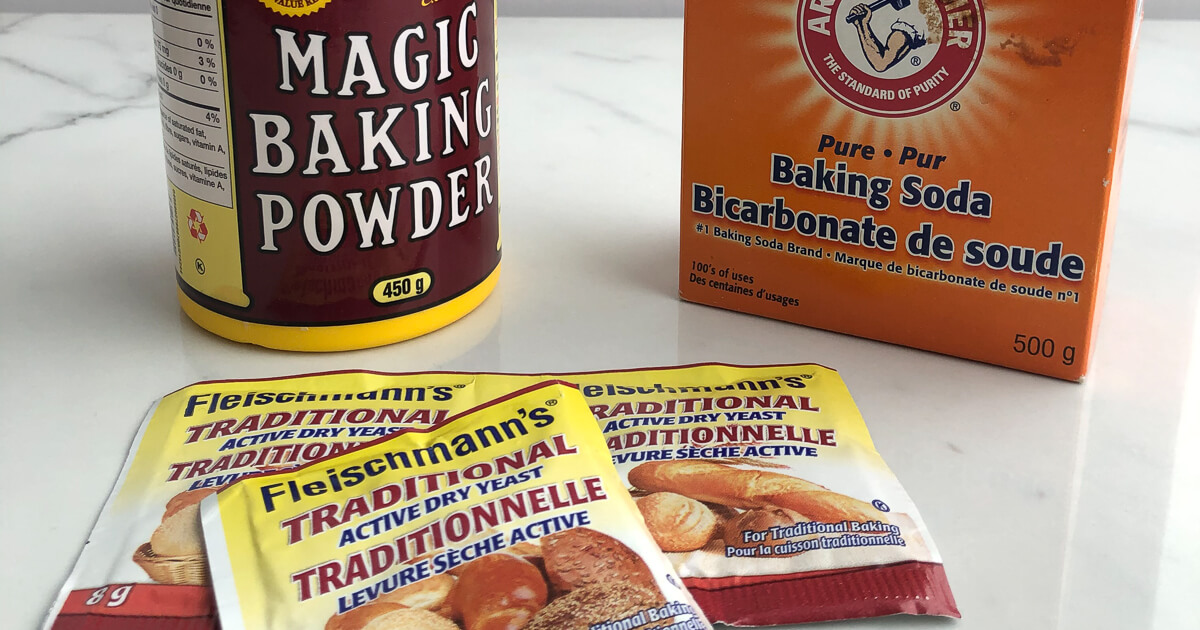 a yellow container of magic baking powder, an orange box of Arm & Hammer, and 3 packets of Fleischman's Active dry yeast