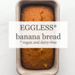 Loaf of eggless banana bread (vegan and dairy-free) in loaf pan on marble surface