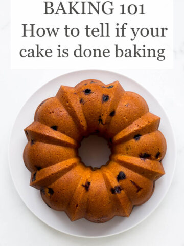 Baking 101 How to tell if your cake is done baking text overlay over picture of golden bundt cake with dried cranberries served on white plate