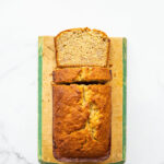 Golden brown banana bread on a vintage wood cutting board with painted green trim