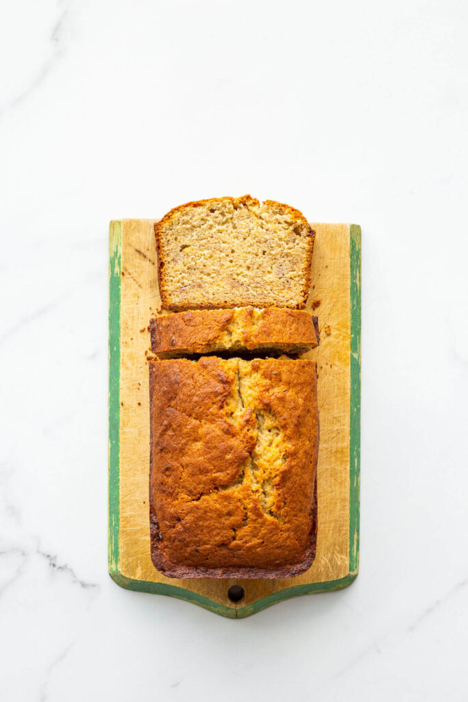 Golden brown banana bread on a vintage wood cutting board with painted green trim.