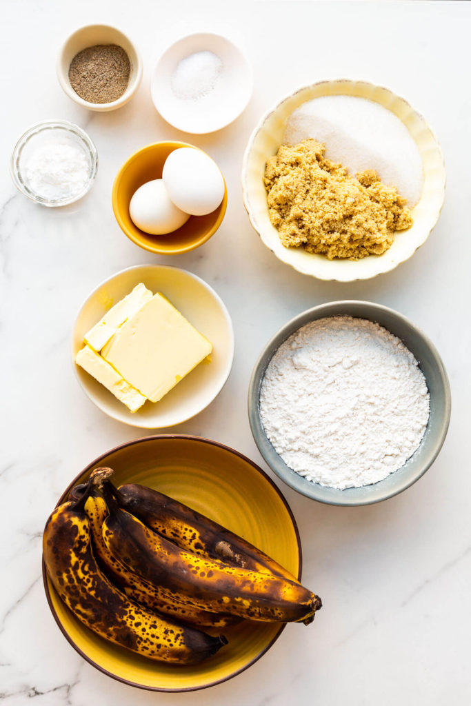Basic banana bread ingredients: butter, sugar, eggs, bananas, flour, baking powder, and salt (cardamom for flavour).