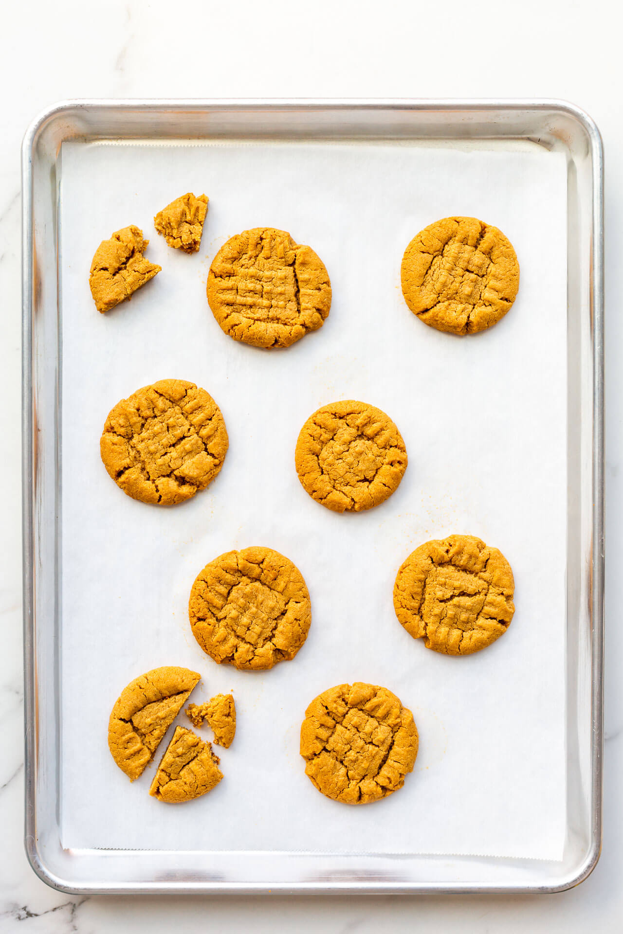 Baked flourless peanut butter cookies on a sheet pan lined with parchment with signature criss cross pattern
