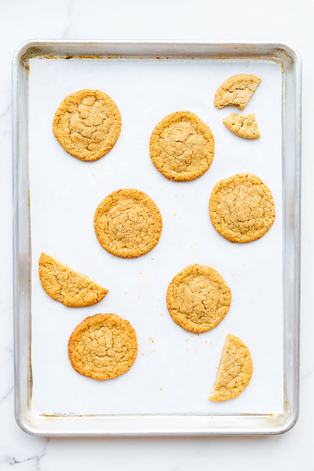 Flourless tahini cookies made with all natural tahini baked on a sheet lined with parchment papaer
