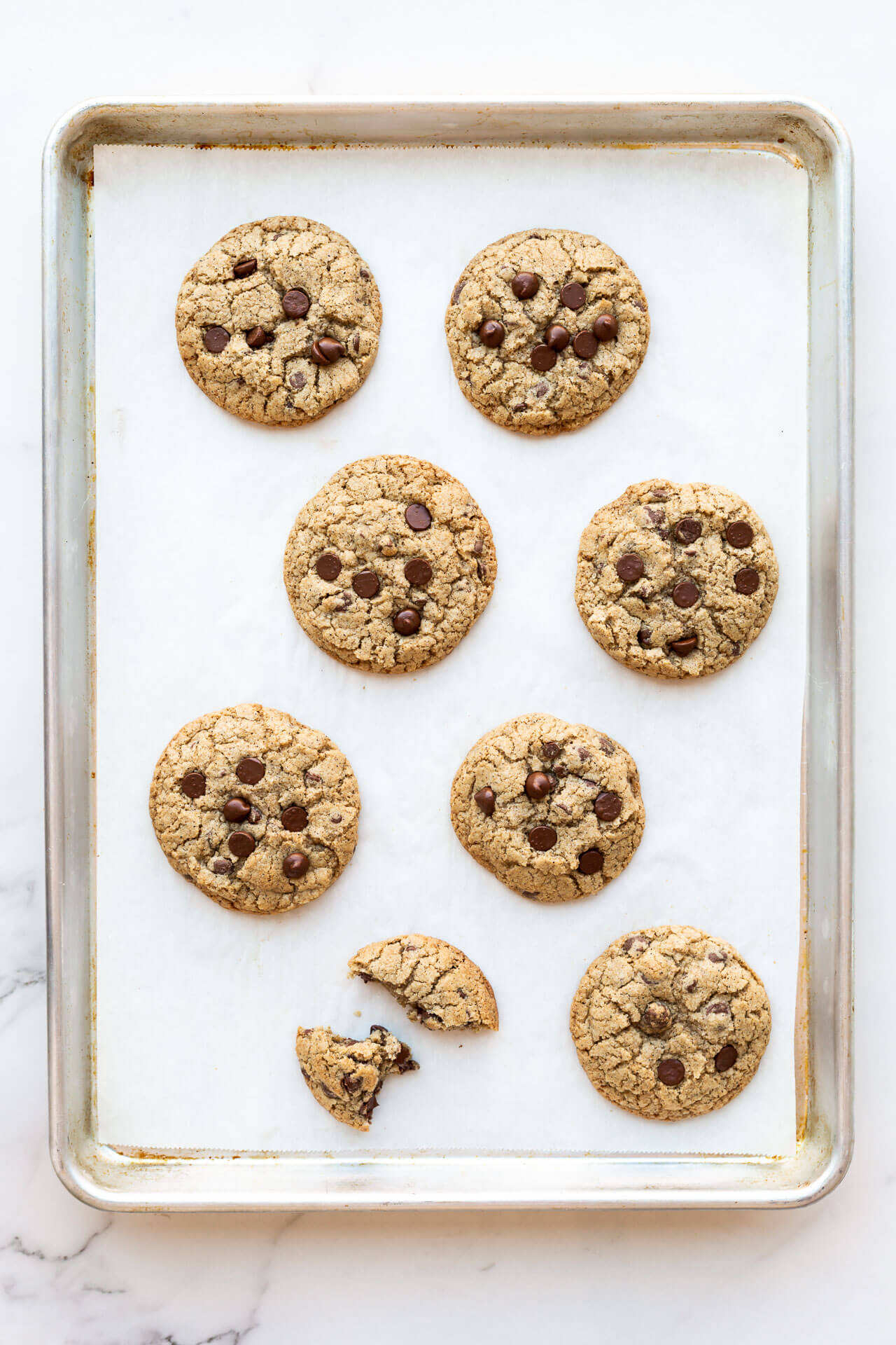 Thick chewy chocolate chip cookies made with buckwheat flour so they are a little greyer in colour compared to all-purpose flour and baked on a parchment lined sheet pan (8 cookies, one of which is broken in pieces)