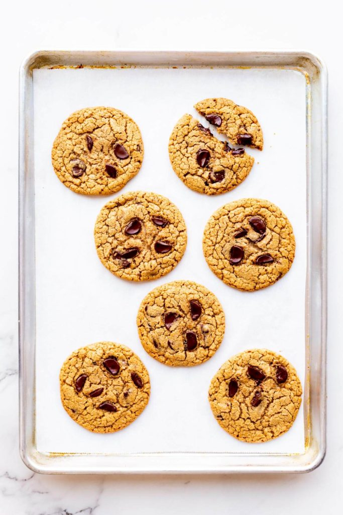 Freshly baked big chocolate chip cookies made with chunks of dark chocolate on a parchment-lined sheet pan with one cookie broken in two — 7 cookies on sheet pan