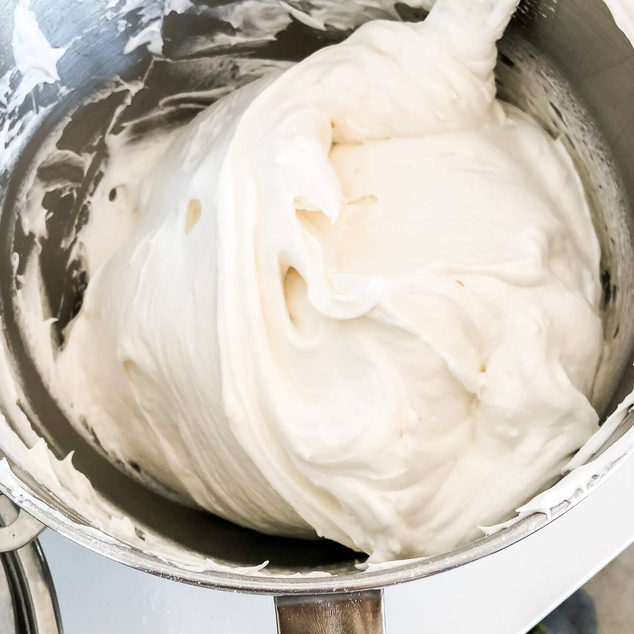 Photo demonstrating folding of whipped egg whites with flour to make angel food cake without deflating the mixture, in a big metal bowl using a large spatula