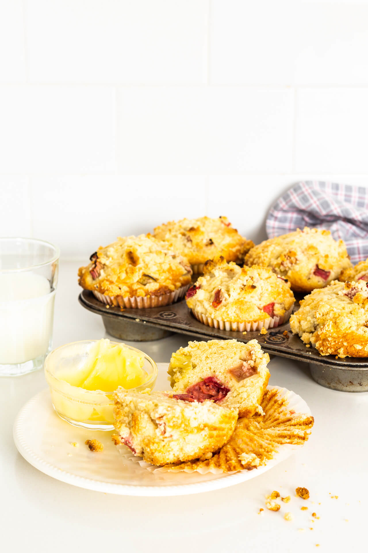 A vintage muffin pan of rhubarb muffins with one on a small plate, cut open to show pink rhurbarb inside, served with a glass of milk