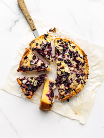 Sliced black currant cake on parchment paper with a wood-handled knife to serve