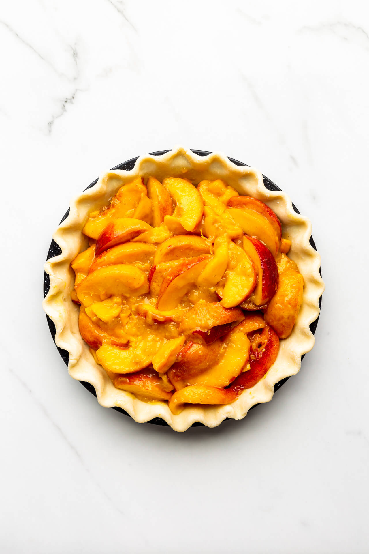 Filled peach mango pie ready for top crust