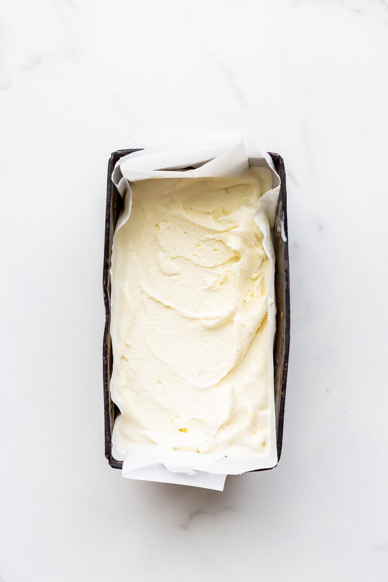 Freshly churned cardamom ice cream transfered to a big dark loaf pan to chill until frozen solid