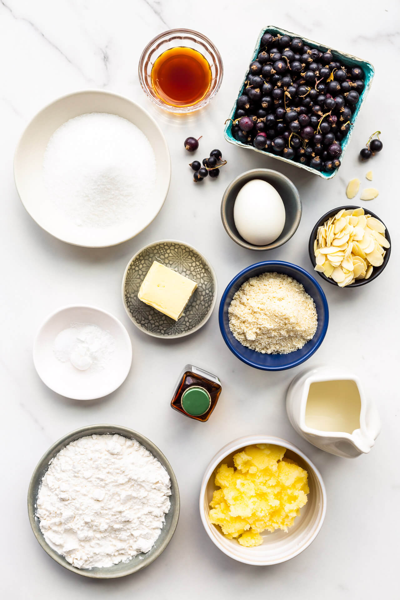Ingredients for black currant cake measured out into small dishes, including black currants, vanilla extract, granulated sugar, egg, butter, ground almond, baking powder, salt, milk, flour, and a sugar paste to make a crispy topping