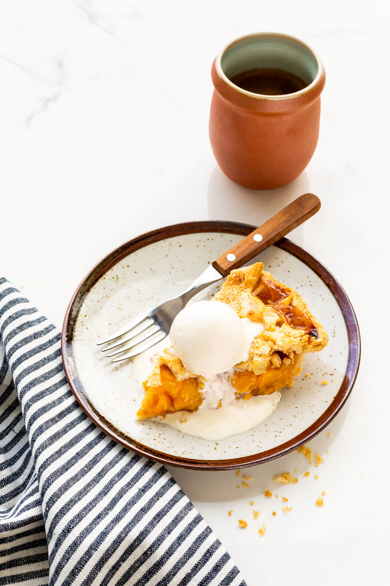 A slice of peach mango pie served à la mode with vanilla ice cream on a ceramic plate with a wood-handled fork and a cup of coffee, blue white striped linen
