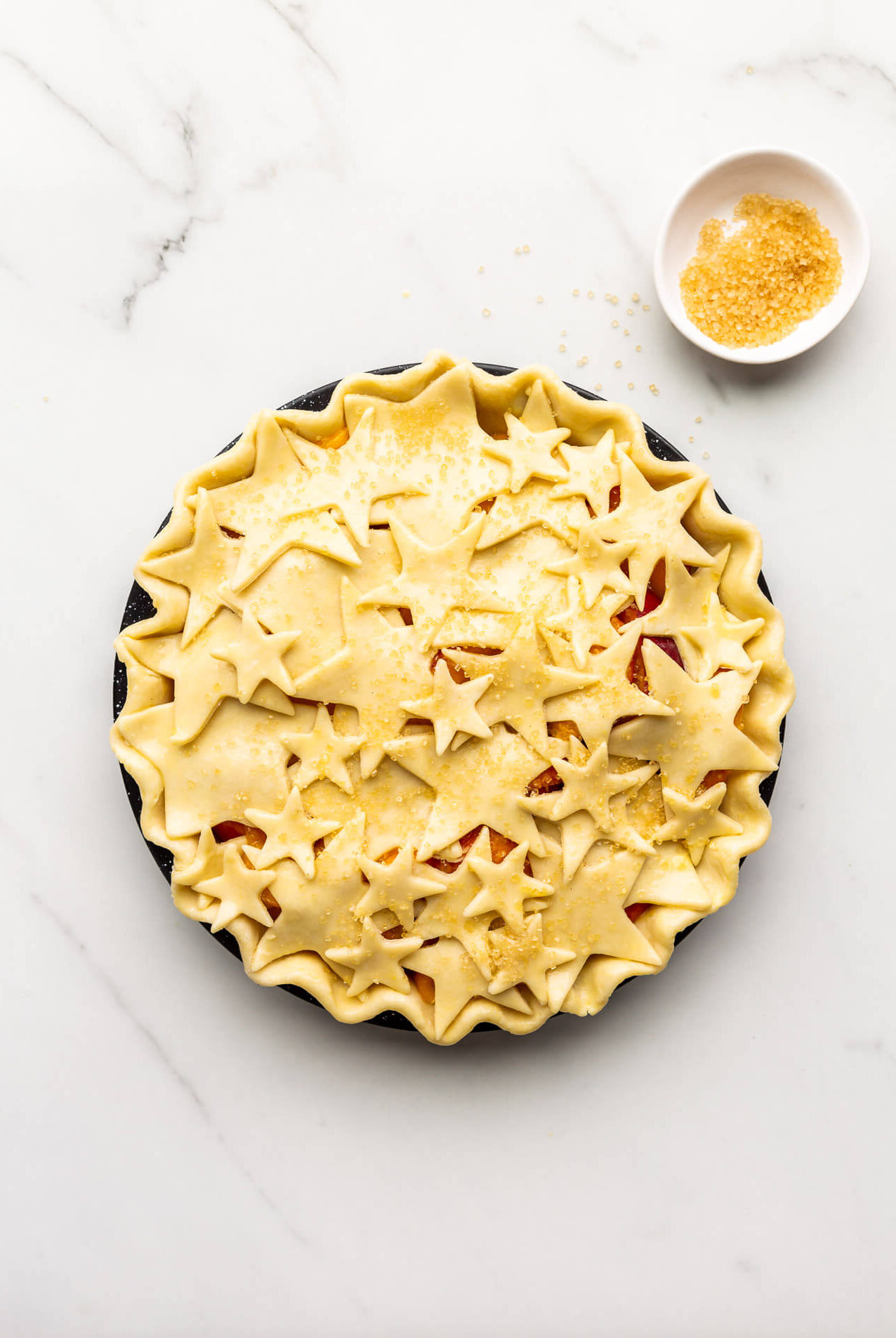 Unbaked pie decorated with star cutouts and sprinkled with turbinado sugar before baking