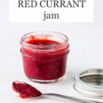 A jar of red currant jam made with strawberries with spoon of jam on side and metal bands