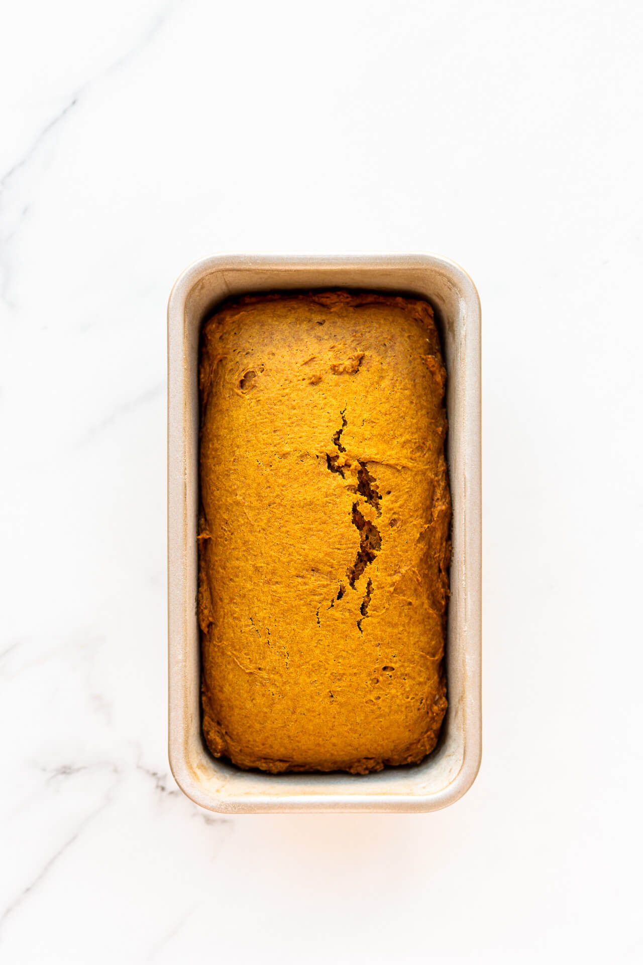 Freshly baked eggless pumpkin bread cooling in the loaf pan it was baked in