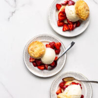 Three ice cream strawberry shortcakes on small dessert plates on white marble surface