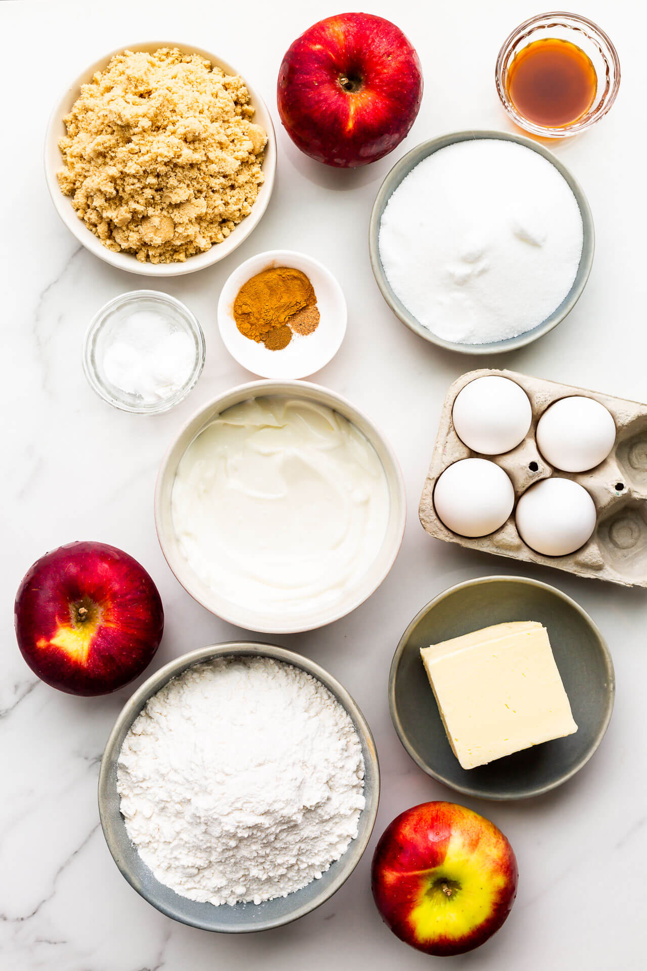 Ingredients to make apple bundt cake measured out including apples, brown sugar, white sugar, spices, sour cream, eggs, salt, baking powder, baking soda, butter, and flour