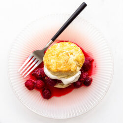 A raspberry shortcake with homemade biscuit, whipped cream, and berries on a pink plate with a fork with black matte handle