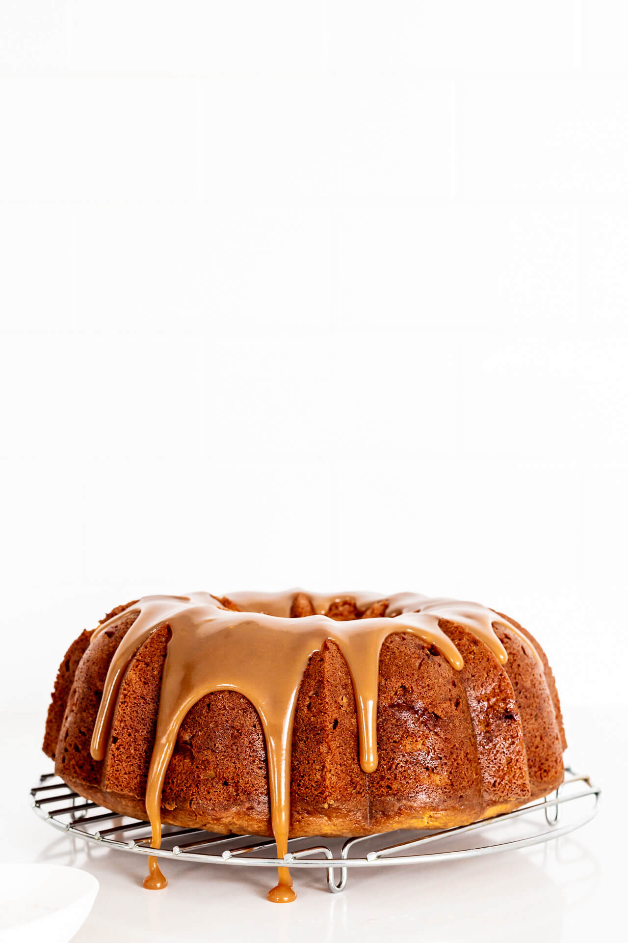 Drizzling salted caramel over a bundt cake set on a wire rack