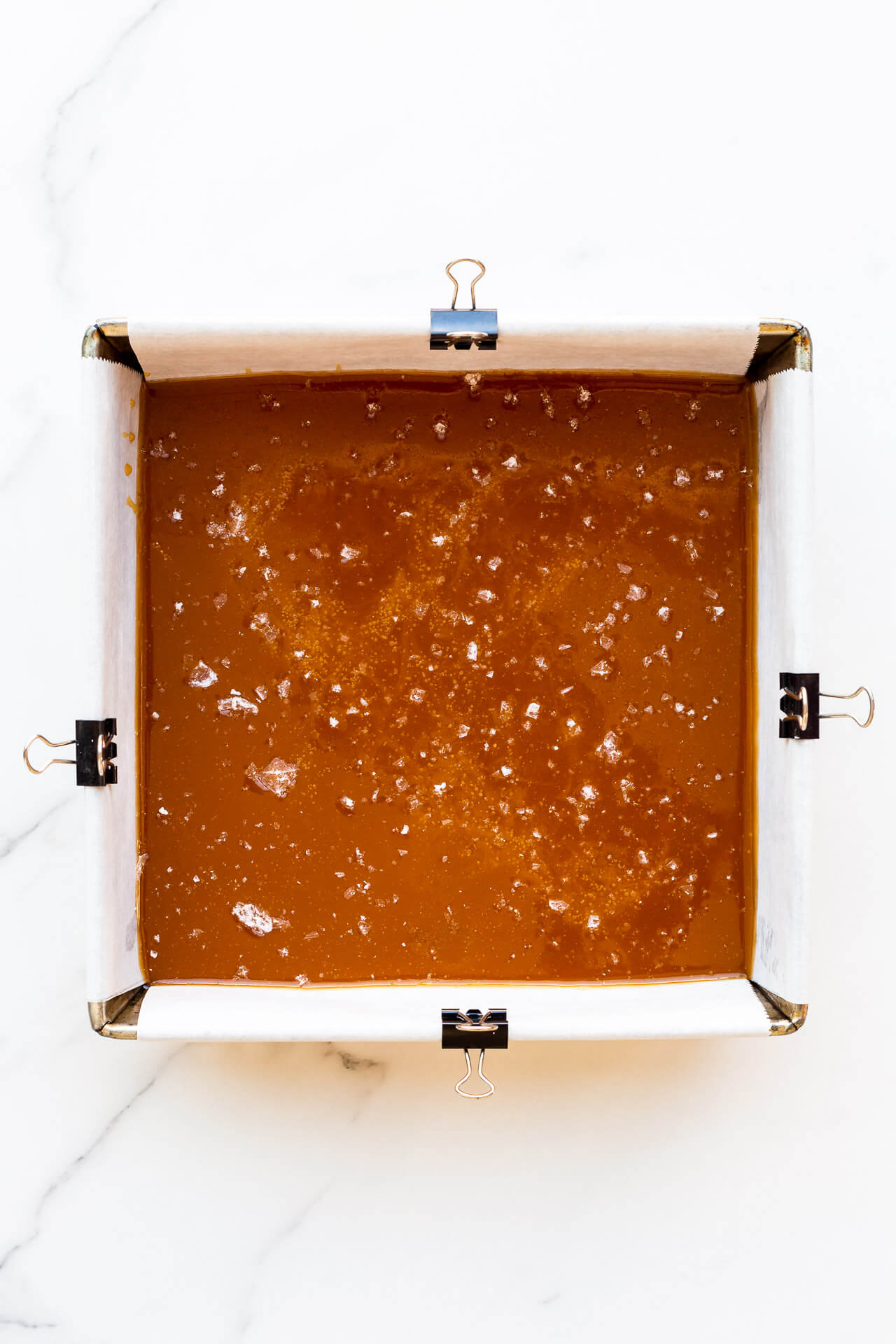 Caramels setting in an 8x8 pan lined with parchment paper clipped to sides of pan to hold it in place