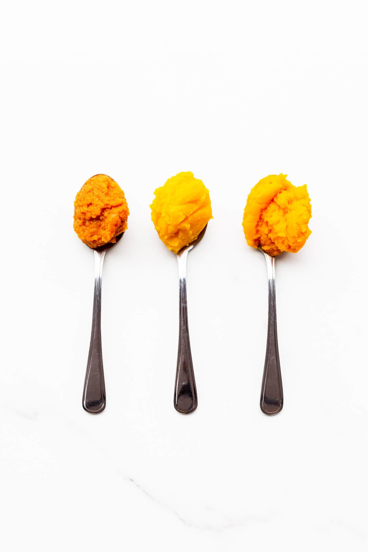 Spoon of canned pumpkin (dark orange) versus homemade sugar pumpkin purée (yellow-orange) versus kabocha squash purée (bright orange)