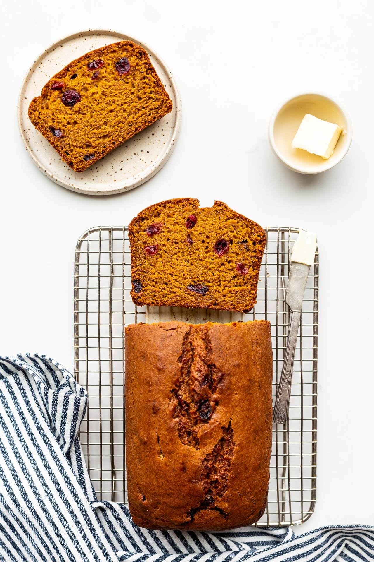 Sliced pumpkin cranberry bread on cooling rack being served with butter