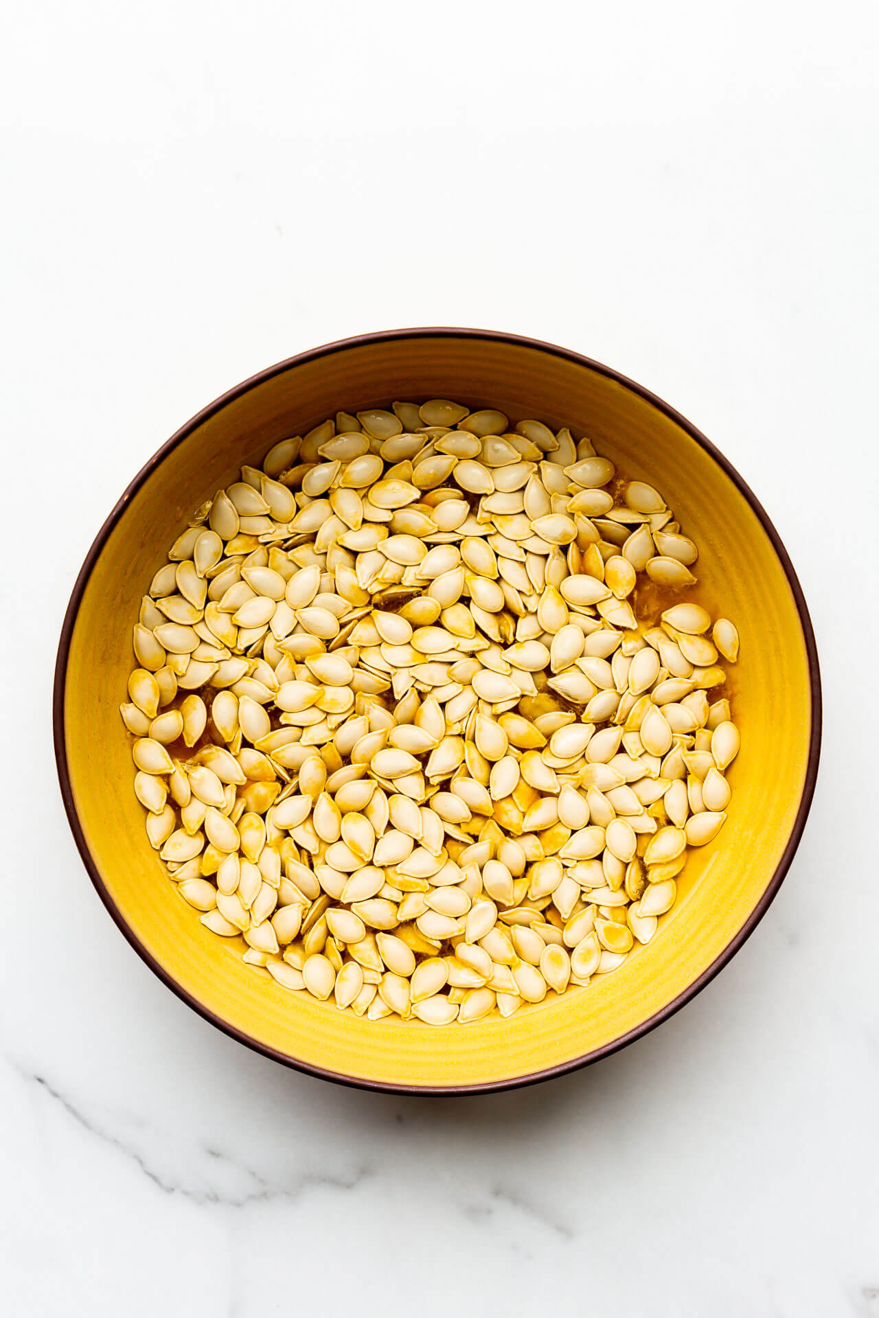 Soak pumpkin seeds in a bowl of water before baking.