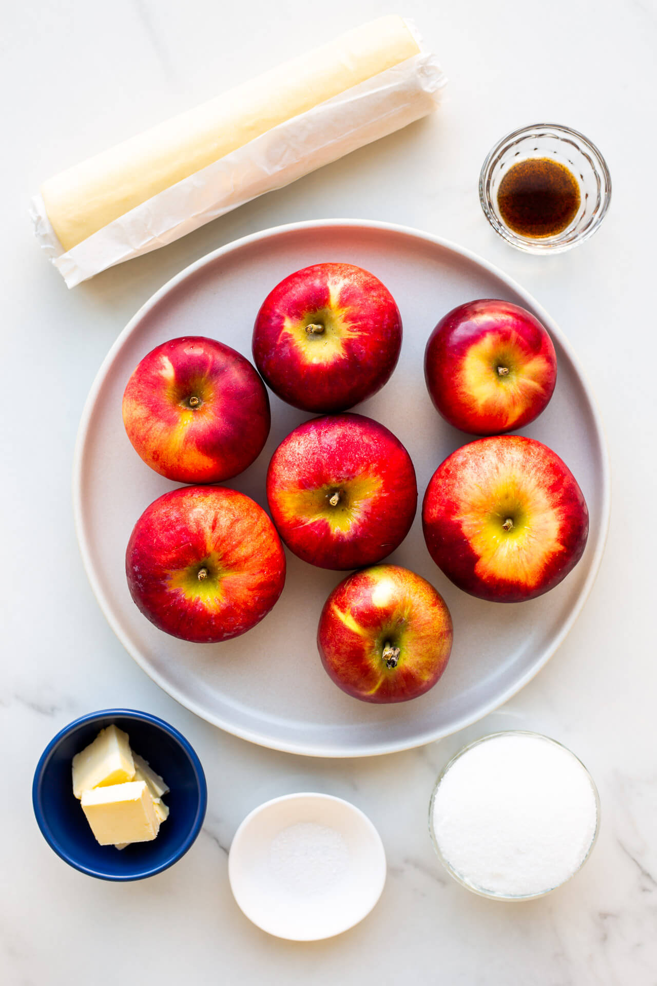 Ingredients to make apple tarte tatin include puff pastry (or pie dough), apples, butter, sugar, a little salt and some vanilla bean paste.