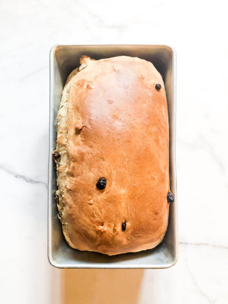 A loaf of stollen bread in a bread pan, freshly baked and golden brown.