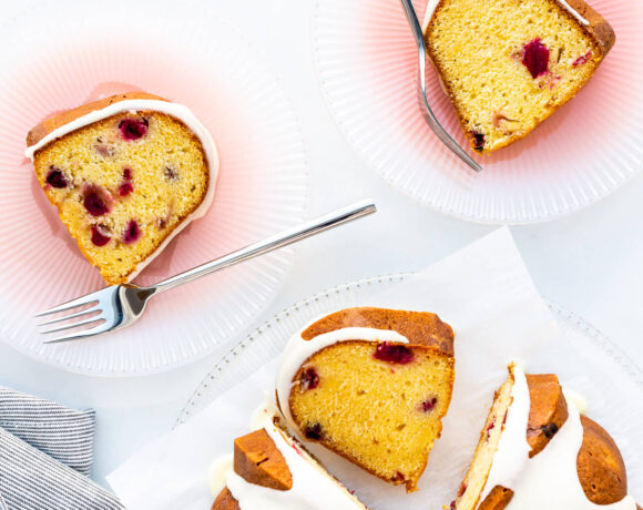 Slices of orange cranberry cake served on pink glass plates with forks.