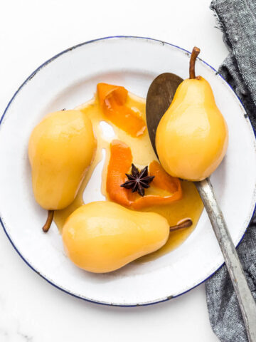 Poached pears on an enamelware plate.
