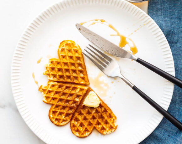 Waffles on a plate with maple syrup and a pat of butter.